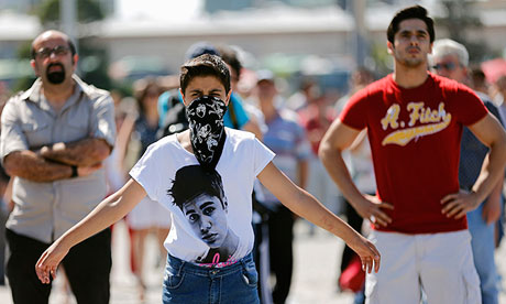 People stand in silent protest at Taksim Square after a man's silent vigil inspired copycat protests