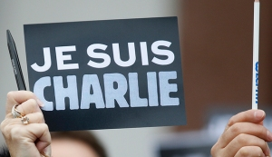 """An employee of the Council of Europe holds a placard which read """"I am Charlie"""" and a pen, during a minute of silence in front of the Council of Europe in Strasbourg"""