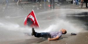 A man is hit by a jet of water as riot police use a water cannon to disperse demonstrators during a protest against Turkey's Prime Minister Tayyip Erdogan and his ruling Justice and Development Party (AKP) in central Ankara June 1, 2013. Erdogan made a defiant call for an end to the fiercest anti-government demonstrations in years on Saturday, as thousands of protesters clashed with riot police in Istanbul and Ankara for a second day. REUTERS/Umit Bektas (TURKEY - Tags: POLITICS CIVIL UNREST TPX IMAGES OF THE DAY)